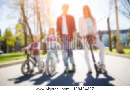 Blurred photo of family on bicycles in park during day