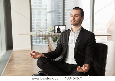 Businessman meditates in lotus position on coach in modern office. Company leader practicing yoga during break at work for strength recovery and stress relief. Man relaxing near workplace with laptop