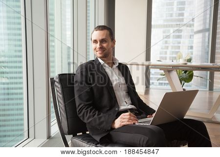 Successful businessman satisfied with work results resting in armchair, looking out of window. Young entrepreneur imagines success in business, dreaming of happy future while sitting in modern office