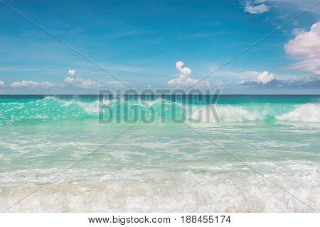 Beautiful ocean surf on tropical beach and blue sky.