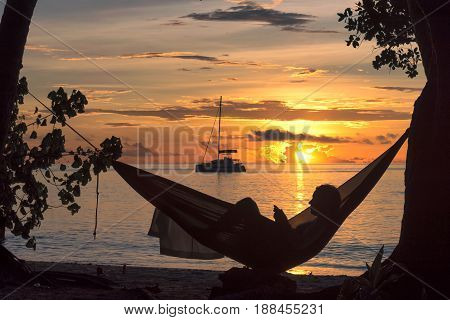 Sunset beach vacations, silhouette of a woman reading in hammock on tropical island.