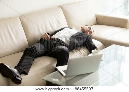Tired businessman lying relaxed on sofa. Man fall asleep on couch in office when stayed at work till late. Entrepreneur takes short break, recovery sleep after too much hard work at project on laptop