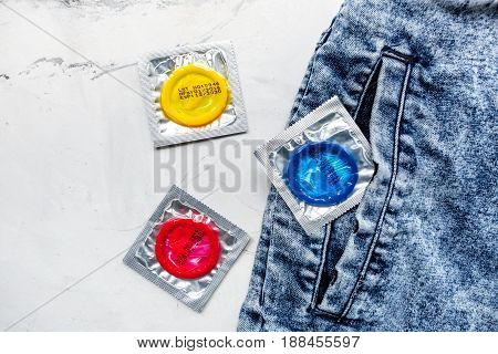male contraception and jeans with condom on white table background top view