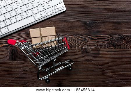 office desk with mini trolley and keyboard for online buying on wooden background top view mock-up