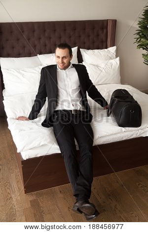 Happy businessman with luggage sitting on bed, relaxing. Man enjoys comfortable apartment on arrival to hotel, happy to return home. Company manager in incentive trip, rewards travel. Business tourism