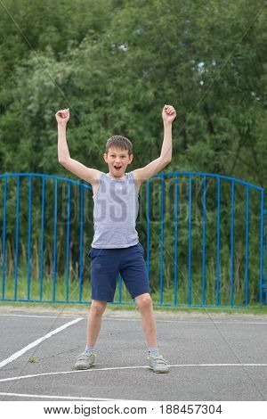 A Teenager In A T-shirt And Shorts Celebrates The Victory