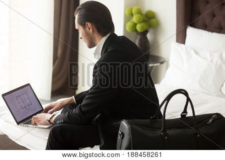 Young independent businessman working from hotel, looking on laptop screen. Executive manager checks documents or construction plan on computer at home before go on business trip. Distance job concept