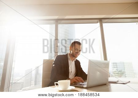 Successful businessman working on laptop in modern luxury office desk. Young entrepreneur satisfied with work result analyzing financial indicators on computer. Man controls company development online