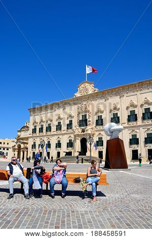 VALLETTA, MALTA - MARCH 30, 2017 - View of the Auberge de Castille in Castille Square with the Bianco Carrara marble sculpture and tourists sitting on a bench in the foreground Valletta Malta Europe, March 30, 2017.