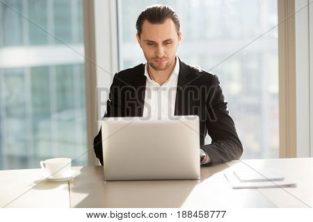 Office worker sitting at desk, working, looking on laptop screen. Businessman surfing Internet information while takes coffee break at workplace. Manager studying customers feedback online, write blog