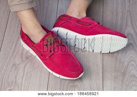 legs with a red leather moccasins on a laminate