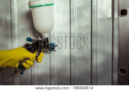 pulverizer in a man's hand with yellow glove on a metal background