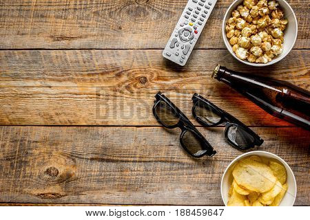 film whatching party with beer, chips and pop corn on wooden background top view mockup
