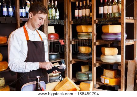 Cheese shop assistant swipe credit card, paying for order of in grocery