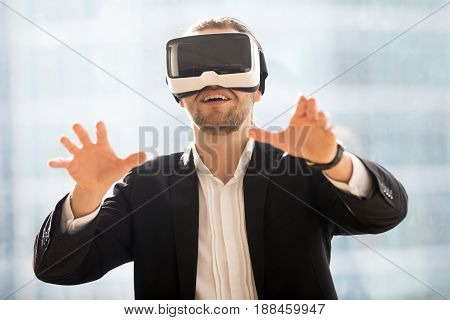 Businessman in virtual reality glasses trying to touch or embrace with hands virtual objects in digital simulation. Young man exited amazing gaming experience in virtual reality with VR headset opportunities