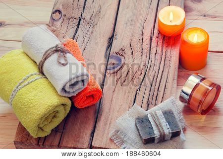SPA with towels, candles, cream and soap on a wooden background