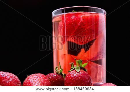 Detox with strawberries and ice on a black background