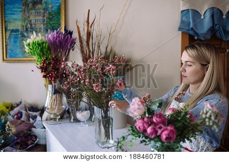 woman florist making bouquet of pink flowers indoor. Female florist preparing bouquet in flower shop