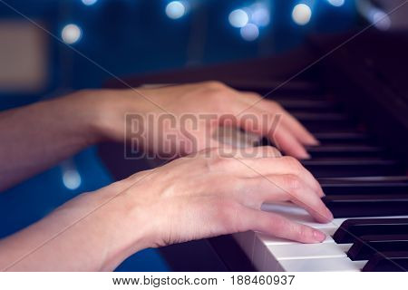 women's hands playing the piano on a blue bokeh background