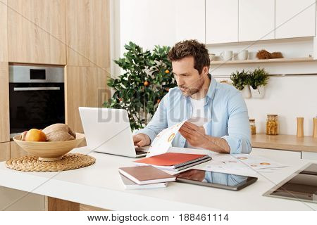 Busy day. Serious concentrated bristled man sitting in a modern kitchen, looking through documents and typing something on laptop at the same time.