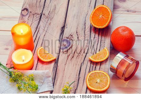 SPA with oranges, candles, cream and flowers on a wooden background
