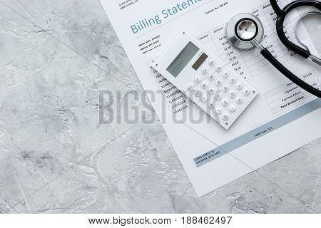 billing statement for for medical service in doctor's office on stone desk background top view mock up