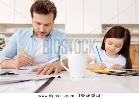 Both inspired. Loving young father and his cute little daughter drawing simultaneously with colored pencils, being on the blurred background, with a white mug being a focus point in the foreground