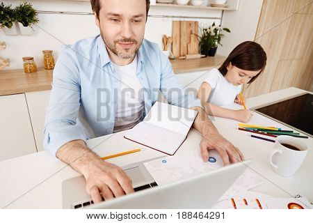 Family harmony. While pleasant smiling single father typing on the laptop with one hand and tracking info on the printout with the other one, his pretty daughter being all focused on drawing.
