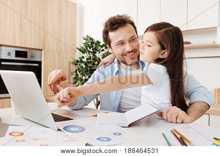 I choose this. Happy young father looking at his daughter with love, pointing at the laptop screen and smiling while the girl hugging him and pointing at the same thing on the screen as if choosing it