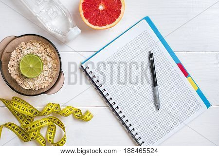 Fresh fruits with tape measure over white wooden background. Fitness concept. Flat lay. Top view. Copy space