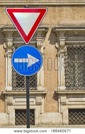 Give way and right arrow direction signals with ancient italian military accademy as background