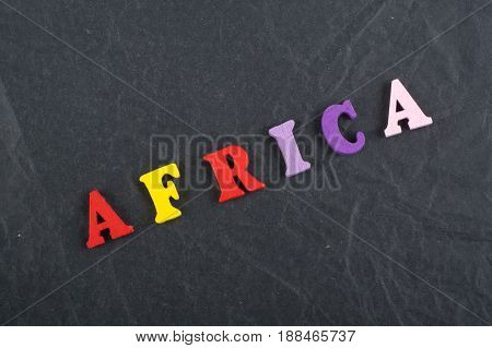 Africa word on blue background composed from colorful abc alphabet block wooden letters, copy space for ad text. Learning english concept