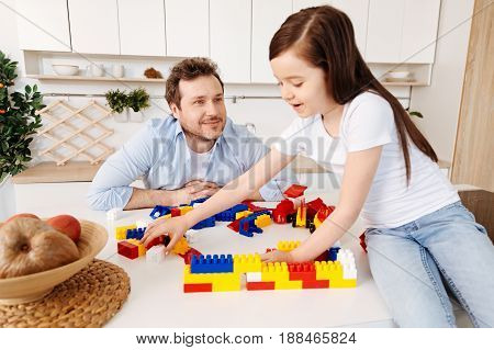 Admiring look. Little girl sitting on the top of the counter and reaching for a part of a construction set while her father looking at her with admiration and fondness