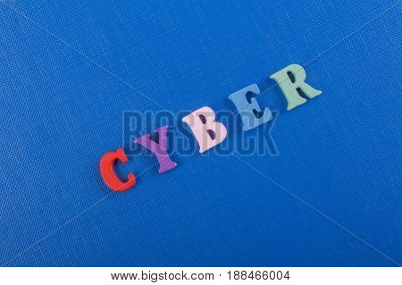 CYBER word on blue background composed from colorful abc alphabet block wooden letters, copy space for ad text. Learning english concept