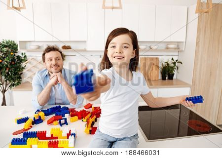 There you go. Cheerful little girl sitting on the kitchen counter and holding out a blue construction set part to the camera while her father resting his chin on the hands and looking at her fondly