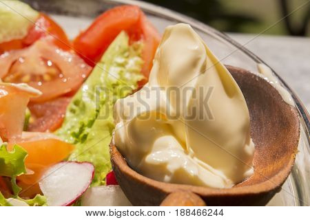 Fresh spring vegetables in a glass bowl with a wooden spoon with mayonnaise on rustik background