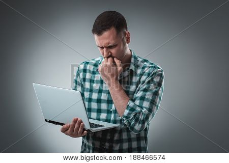 Frustrated businessman holding a laptop covers his face with his hand on gray background. Business theme