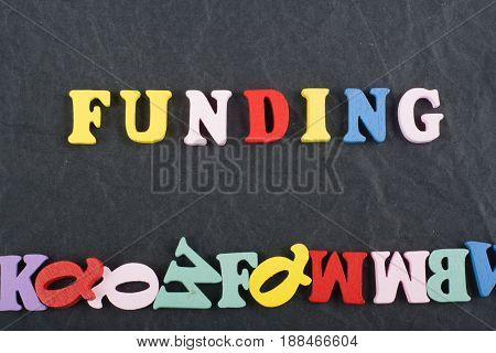 FUNDING word on black board background composed from colorful abc alphabet block wooden letters, copy space for ad text. Learning english concept