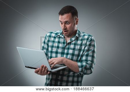 Businessman holding a laptop on gray background. The man emotionally reacts to the inscriptions in the laptop