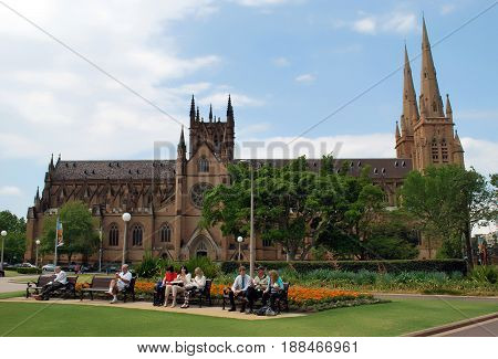 SYDNEY AUSTRALIA - OCTOBER 28 2013: Sydney residents and tourists enjoying midday on the benches of Hyde park in front of St. Mary's Cathedral