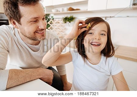 Cute new accessory. Gorgeous little girl standing next to her smiling dad and pressing a piece of a bow-tie pasta to her hair as if having a hairpin