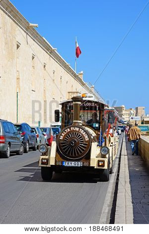 VALLETTA, MALTA - MARCH 30, 2017 - Tourist land train passing the Holy Infirmary along Triq Il-Mediterran Valletta Malta Europe, March 30, 2017.