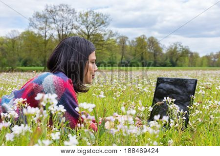Woman with laptop lying in meadow with flowers