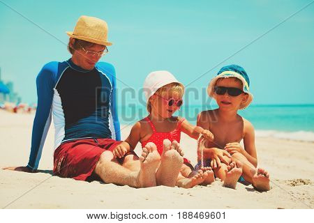 father with son and daughter play on sand beach