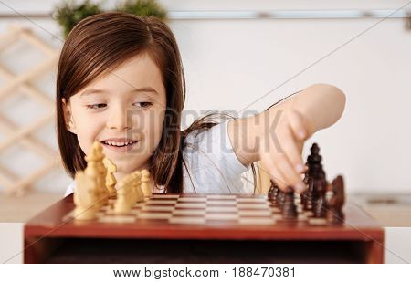 Having fun alone. Pretty little girl sitting alone near the chessboard, looking at the pieces with a mischievous smile and moving the pieces by herself