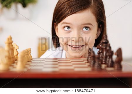 Genuine emotions. Gorgeous little girl with beautiful grey eyes keeping her face close to the chessboard, looking up and smiling at someone.