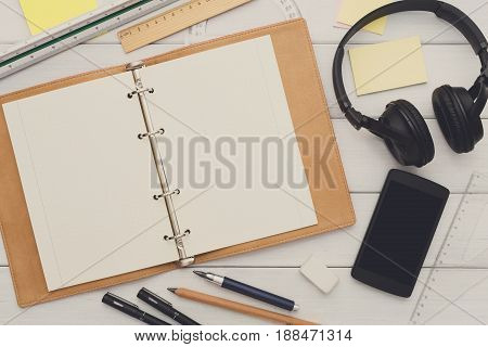 Education and work concept, top view shot of workplace. Stationery supplies - blank notepad and headphones on white wooden desktop, flat lay, copy space, mockup