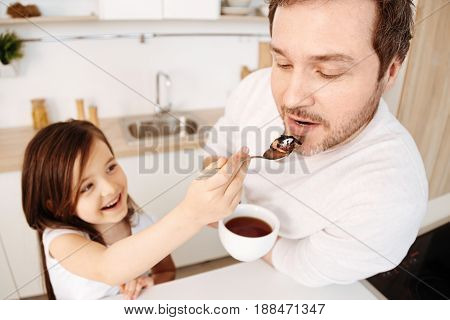 Daughterly care. Affectionate smiling daughter feeding her dear father from a teaspoon with a bit of cake while he holding a cup of tea and waiting for a treat with an open mouth