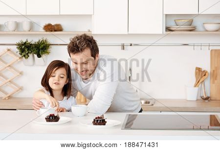 Bon appetit. Young loving father hugging his sweet little daughter and watching her taking a spoonful of a chocolate cake while standing near the kitchen counter