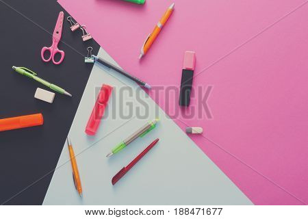 Stationery supplies and devices on pop art background. Top view flat lay mockup of creative work space at modern office with markers, rubbers, pens, scissors and binder clips